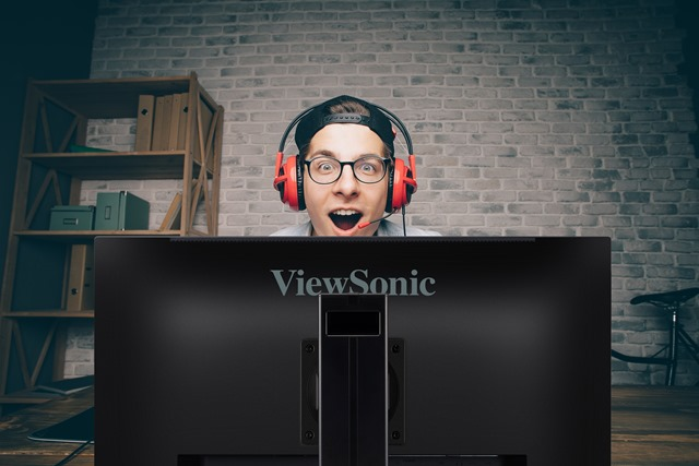 Young man playing game at home and streaming playthrough or walkthrough video. Stylish guy is surprised with one intresting game in vr. He is wearing eyeglasses, black cap and red headphones